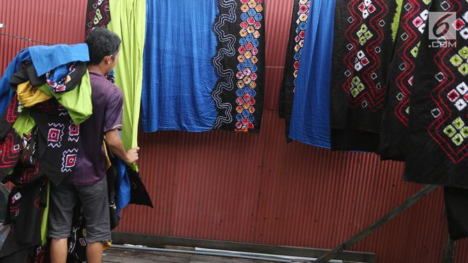 Pekerja mengangkat kain sasirangan yang telah dijemuri di kawasan Banjarmasin, Kalimantan Selatan, Senin (26/3). Kain sasirangan ini diwariskan secara turun temurun sejak abad XI. (Liputan6.com/Immanuel Antonius)