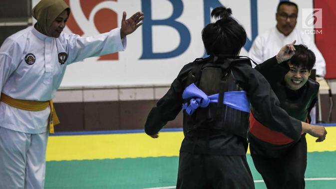 Pesilat Nirmalasari Oktaviani (kanan) beradu jurus dengan pesilat Laos Olathai Sounthavong di semifinal 50-55 kg putri cabang Pencak Silat 18th Asian Games Invitation Tournament, Jakarta, Senin (12/2). Indonesia menang 5-0. (Liputan6.com/Faizal Fanani)