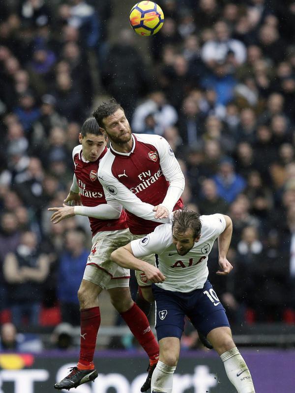 Harry Kane (kanan) saat berebut bola dengan dua pemain Arsenal pada lanjutan Premier League di Wembley stadium, London, (10/2/2018). Tottenham menang tipis 1-0 atas Arsenal. (AP/Tim Ireland)