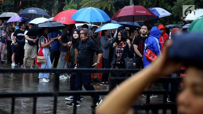 Penonton mengenakan payung karena hujan saat mengantre tiket masuk konser Liam Gallagher di Ecovention Ancol, Jakarta Utara, Minggu (14/1). Liam Gallagher siap menghibur para penggemarnya selama 90 menit. (Liputan6.com/JohanTallo)