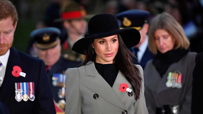 Meghan Markle dan tunangannya Pangeran Harry saat menghadiri kebaktian Anzac Day di Hyde Park Corner di London (25/4). Anzac Day adalah hari peringatan kebangsaan yang dirayakan di Australia dan New Zealand. (Toby Melville/Pool Photo via AP)