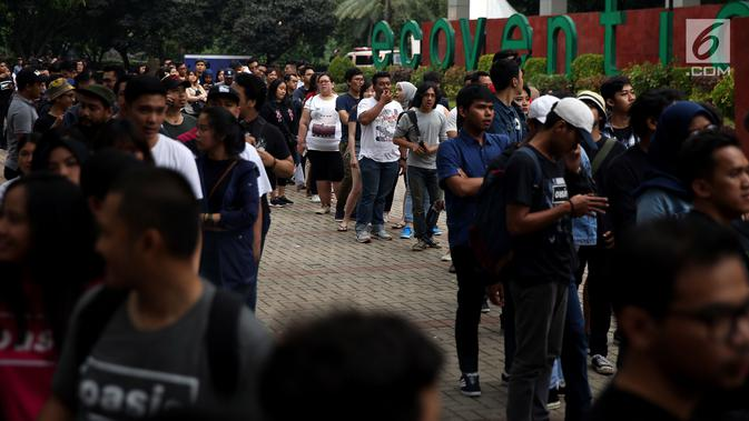 Penonton mengantre tiket masuk konser Liam Gallagher di Ecovention Ancol, Jakarta Utara, Minggu (14/1). Antrean di loket tiket pembelian dan penukaran sudah mulai memanjang sejak sore. (Liputan6.com/JohanTallo)