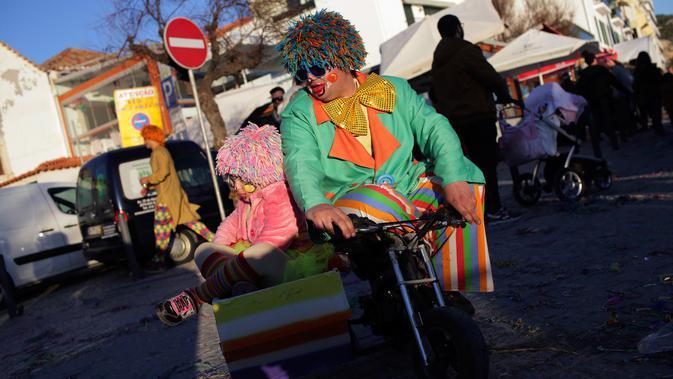 Seorang pria bersama anaknya mengenakan kostum badut saat mengikuti Parade Karnaval Clowns di pantai Sesimbra, Lisbon, Spanyol (12/2). Acara ini digelar setiap tahun. (AP Photo / Armando Franca)