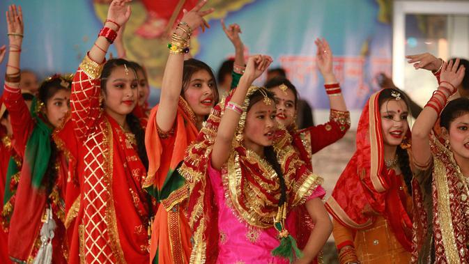 Gadis-gadis India berpakaian tradisional menari saat mereka merayakan festival Lohri di Jammu, India (13/1). Beberapa orang percaya bahwa perayaan tersebut untuk memperingati terjadinya titik balik musim dingin. (AP Photo / Channi Anand)