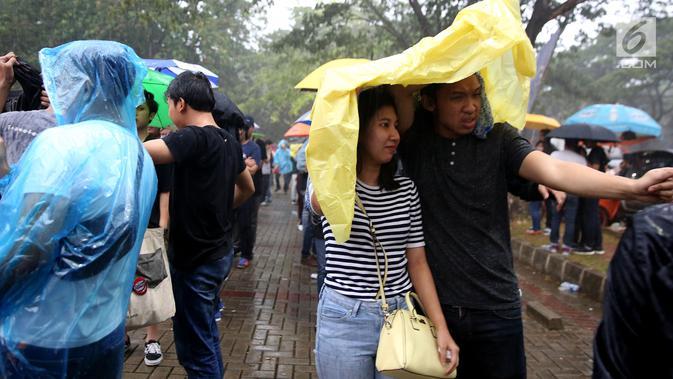 Penonton mengenakan jas hujan saat mengantre tiket konser Liam Gallagher di Ecovention Ancol, Jakarta Utara, Minggu (14/1). Selain penggemar dari kalangan umum, sejumlah selebritis dikabarkan akan meramaikan konser tersebut. (Liputan6.com/JohanTallo)