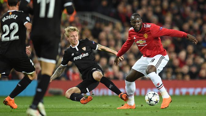 Bek Sevilla, Simon Kjaer berebut bola dengan striker Manchester United, Romelu Lukaku pada laga leg kedua 16 besar Liga Champions di Old Trafford, Selasa (13/3). Manchester United terhempas dari Liga Champions setelah kalah 1-2. (Oli SCARFF/AFP)