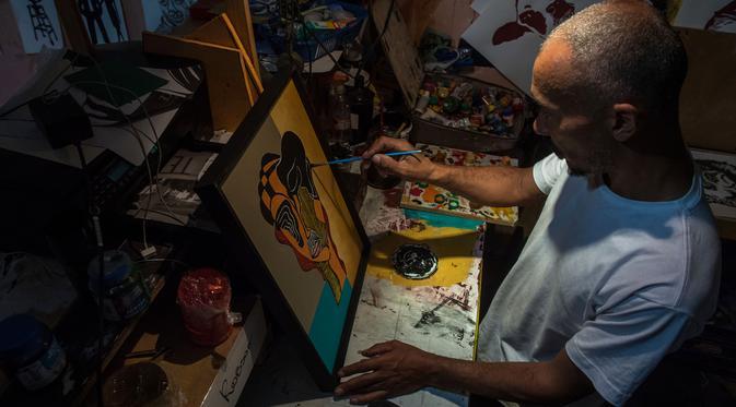 Seniman Brasil D'Julia Gangary sedang membuat lukisan di gedung 'Ocupa Ouvidor 63' di Sao Paulo, Brasil (28/6). Gedung tersebut merupakan gedung terbekelai yang kini ditempati oleh sekitar seratus seniman dari berbagai kelompok. (AFP Photo/Nelson Almeida)