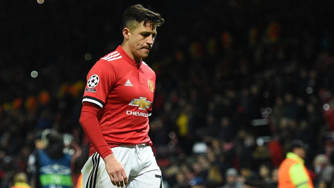 Striker Manchester United, Alexis Sanchez tertunduk sambil berjalan usai kalah dari Sevilla pada leg kedua 16 besar Liga Champions di Old Trafford, Selasa (13/3). Hasil ini membuat langkah Manchester United di Liga Champions terhenti. (Oli SCARFF/AFP)