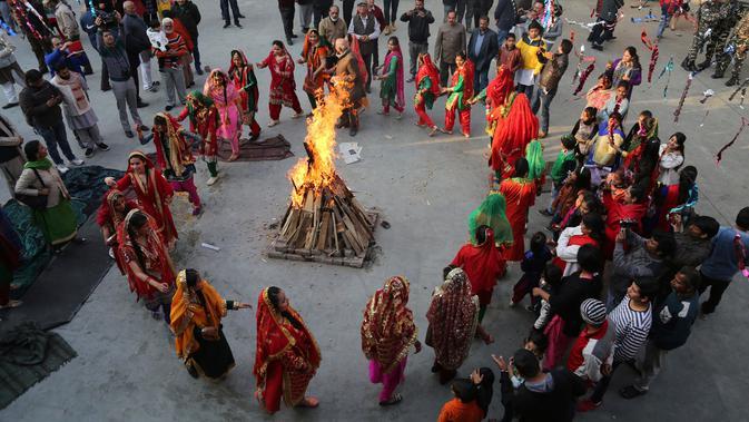 Gadis-gadis India berpakaian tradisional menari mengelilingi api unggun saat merayakan festival Lohri di Jammu, India (13/1). Festival Lohri ini banyak dirayakan oleh orang-orang dari wilayah Punjab di Asia Selatan. (AP Photo / Channi Anand)