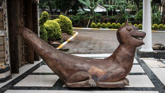 Patung bernama 'Laughing Dragon' yang diciptakan oleh pemahat Edward Njenga terpampang di pintu masuk rumahnya di Nairobi, Kenya, Senin (12/3). (AFP PHOTO/Yasuyoshi CHIBA)