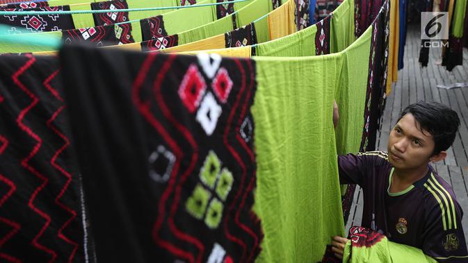Seorang pekerja menjemur kain sasirangan di kawasan Banjarmasin, Kalimantan Selatan, Senin (26/3). Kain sasirangan ini merupakan kain adat suku Banjar di Kalimantan Selatan. (Liputan6.com/Immanuel Antonius)