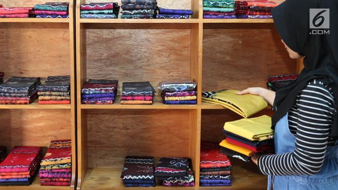 Seorang pekerja menanta kain sasirangan yang siap dijual di kawasan Banjarmasin, Kalimantan Selatan, Senin (26/3). Kain sasirangan ini juga dijadikan cendera mata dan oleh-oleh asli Kalimantan Selatan. (Liputan6.com/Immanuel Antonius)