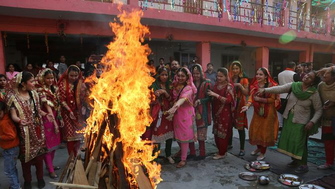 Gadis-gadis India melempar kacang ke api unggun saat mereka merayakan festival Lohri di Jammu, India 13/1). Festival Lohri ini banyak dirayakan oleh orang-orang dari wilayah Punjab di Asia Selatan. (AP Photo / Channi Anand)