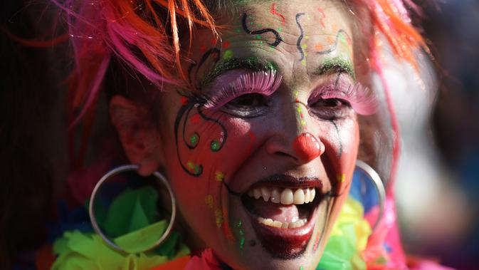 Ekspresi peserta yang mengenakan kostum badut saat mengikuti Parade Karnaval Clowns di pantai Sesimbra, Lisbon, Spanyol (12/2). Ribuan orang mengenakan kostum badut turut memeriahkan karnaval ini. (AP Photo / Armando Franca)